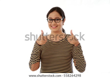 Young woman showing thumbs up gesture against white background