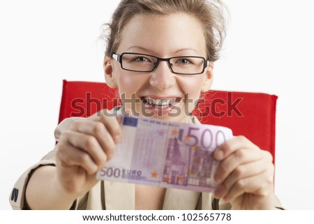 Young woman shows joyfully five hundred euro note - stock photo