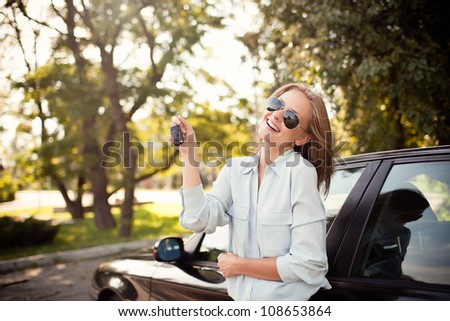 Young woman shows the keys to her new car. Selective focus.