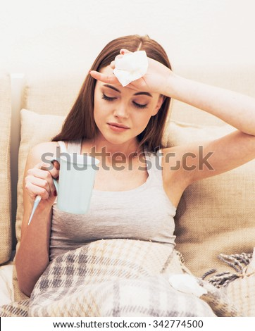 Young woman sick in bed with temperature drinks hot  - stock photo