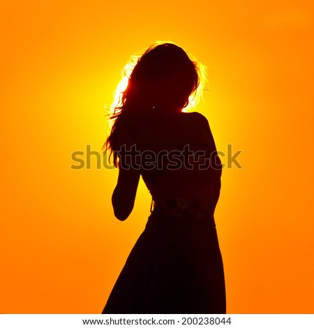 young woman silhouette at sunset - stock photo