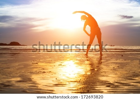 Young woman silhouette exercise on the beach at sunset.