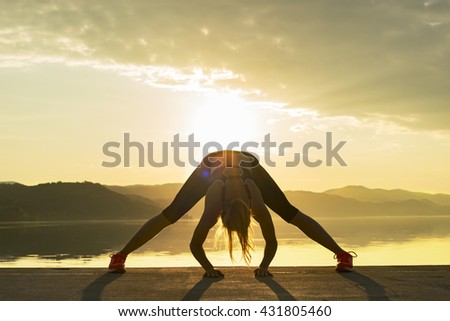 Young woman silhouette practicing yoga by the water at sunset .