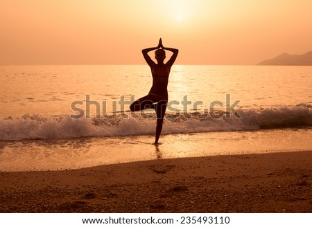 Young woman silhouette practicing yoga on the sea beach at sunset - stock photo