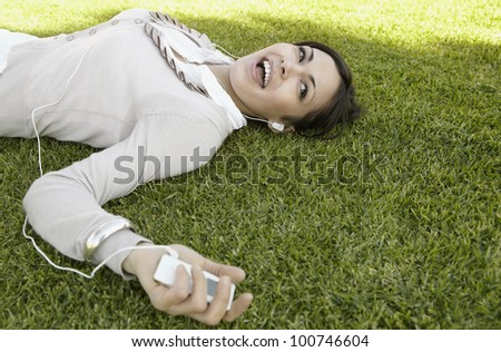 Young woman singing along to the music she's hearing on her headphones, laying down on green grass. - stock photo