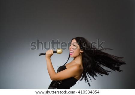 Young woman singing in karaoke club - stock photo
