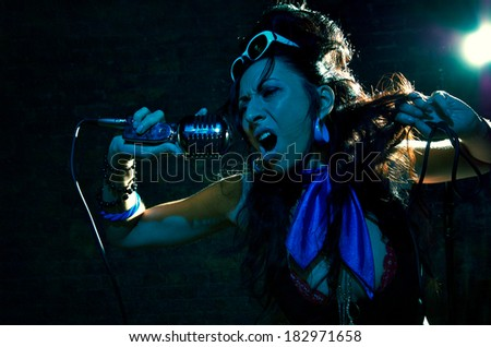 Young woman singing into the microphone against dark background