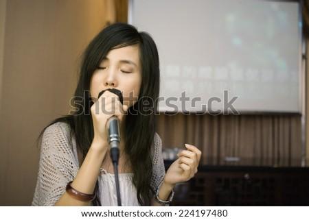Young woman singing karaoke, eyes closed - stock photo