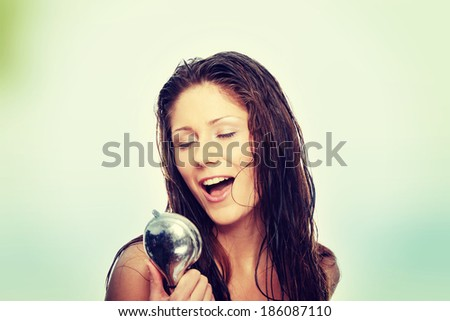 Young woman singing under shower - stock photo