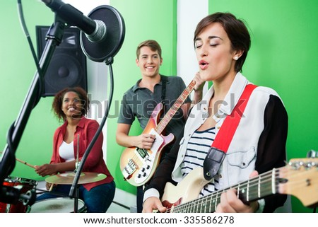 Young woman singing while band playing musical instrument in recording studio - stock photo