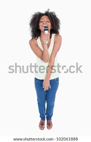 Young woman singing with a cordless microphone against a white background - stock photo