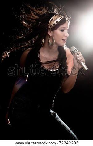 Young woman singing with microphone with back light and flying hair - stock photo