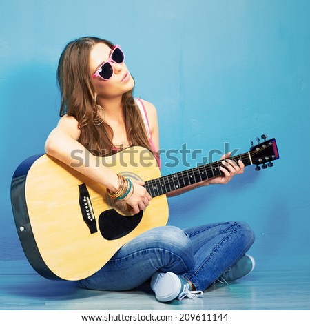 young woman sings and playing guitar . sitting against blue - stock photo