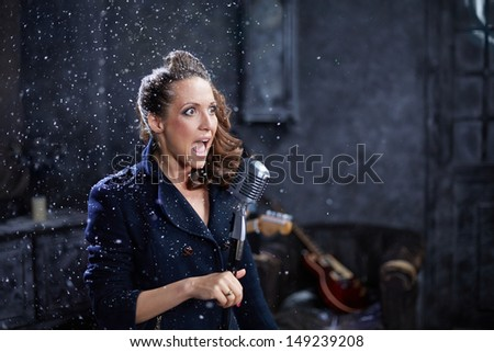 Young woman sings into microphone during shooting musical clip - stock photo