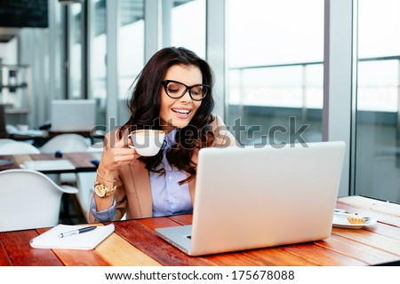 Young woman sipping coffee and using her laptop
