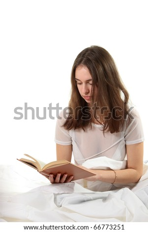 Young woman sit in a bed and read book