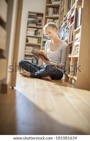young woman sit on the floor reads a book near home library - stock photo