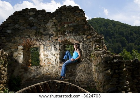 Young woman siting on medieval ruins - stock photo