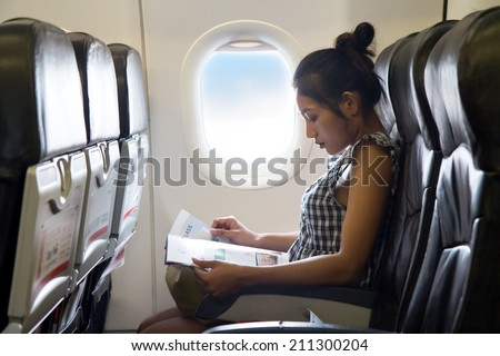 Young woman sits in a chair of the airplane. Woman travels on the plane. Passengers woman reads a magazine in the window of the flying aircraft. Enjoy - entertainment on board of flying air plane. - stock photo
