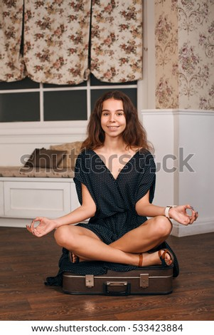 Young woman sits in a pose of yoga on suitcase.