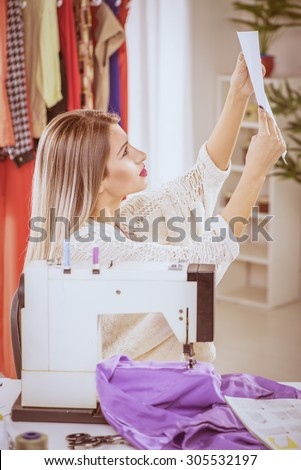 Young woman sits in front of the sewing machine and looking at sketches of clothing.