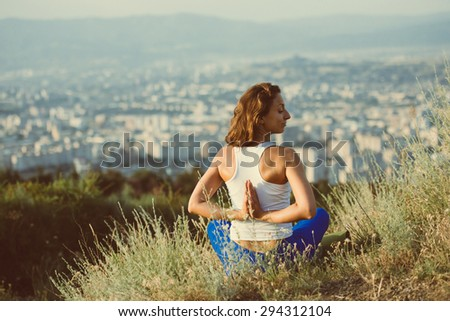 Young woman sits in namaste yoga pose with city on background. Freedom concept. Calmness and relax, woman happiness. Toned image - stock photo