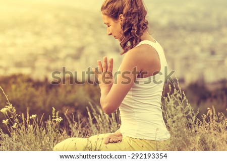 Young woman sits in yoga pose with city on background. Freedom concept. Calmness and relax, woman happiness. Toned image - stock photo