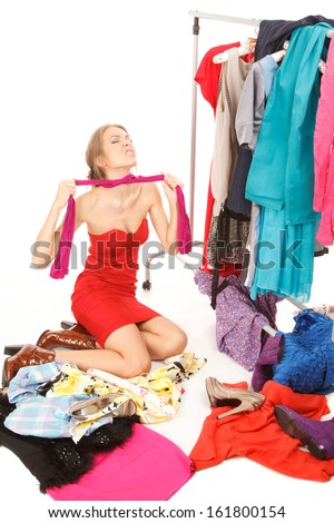 Young woman sits near her clothes rack with lots of dresses,and some clothes is on the floor,and she is choking her self with her pantyhose - stock photo