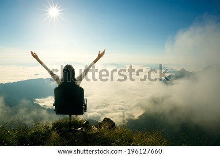 Young woman sits on a chair and open her arms at the top of the mountain, Success in business concept - stock photo