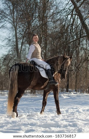 Young woman sits on horseback in spring forest