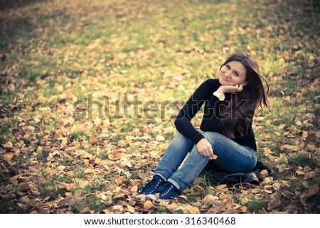 young woman sits on leaves in autumn park - stock photo