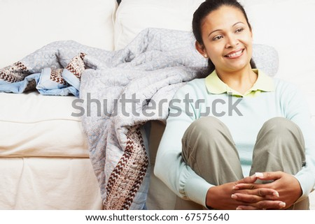 Young woman sitting against the couch