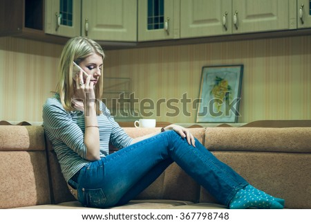 Young woman sitting alone and talking on phone  - stock photo
