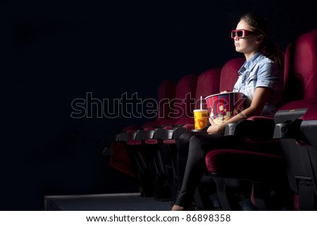 young woman sitting alone in the cinema and watching a movie - stock photo