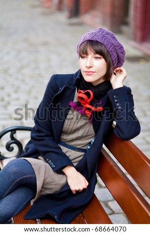 young woman sitting alone on street bench and thinking