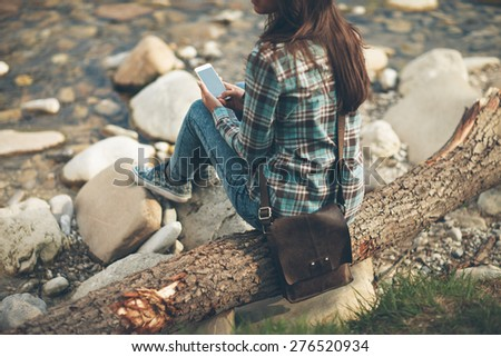 Young woman sitting along the river on a wooden trunk and texting with her mobile phone - stock photo