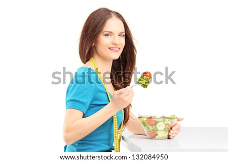 Young woman sitting and eating a fresh salad isolated on white background