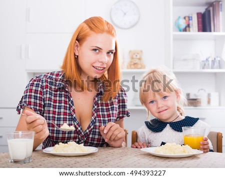 Young woman sitting and feeding daughter with porridge on kitchen indoors