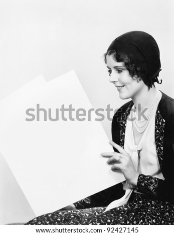 Young woman sitting and holding a sign - stock photo