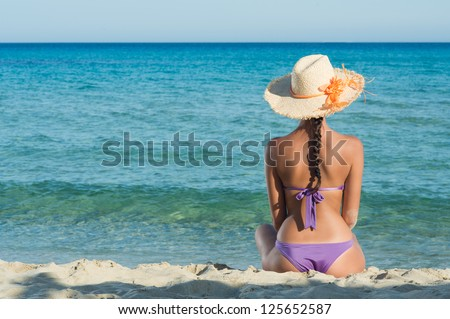 Young Woman Sitting And Looking At Sea