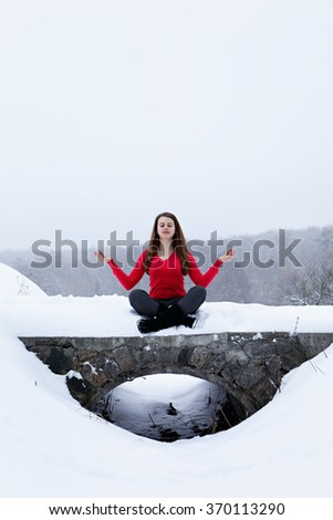 Young woman sitting and meditating at the park in winter - stock photo