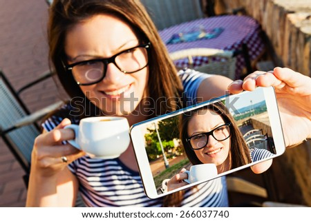 Young woman sitting at a cafe terrace, drinking coffee and taking selfportrait - stock photo