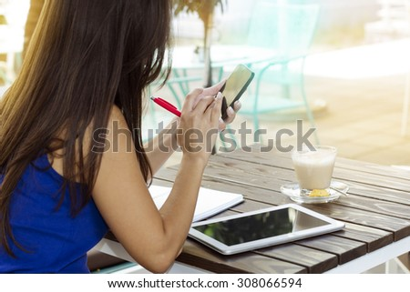 Young woman sitting at a desk sitting in a cafe and using a smart phone outdoors. - stock photo