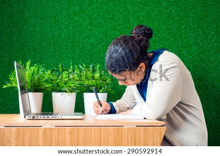 Young woman, sitting at a desk with a laptop in front of her, concentrated, writing down notes on a note pad - stock photo
