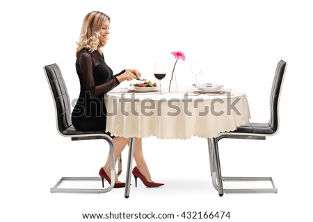 Young woman sitting at a restaurant table and eating dinner alone isolated on white background - stock photo