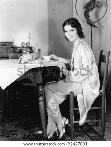 Young woman sitting at a table having breakfast tea