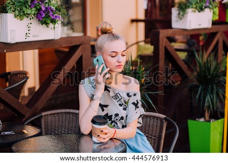 Young woman sitting at a table in a cafe, drinking coffee and talking on the phone. Film processing.