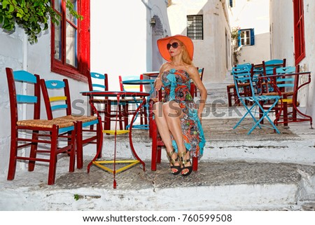 young woman sitting at a traditional cafe of Chora in Amorgos island, Greece