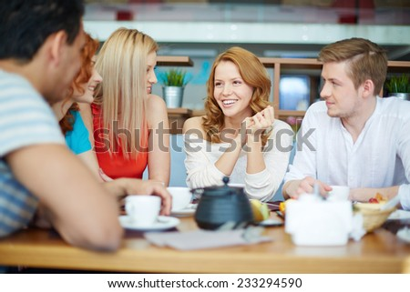 Young woman sitting at caf���© among her friends - stock photo