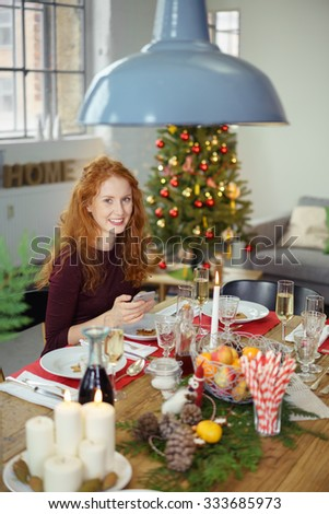 young woman sitting at christmas dinner writing a message for christmas on her smartphone